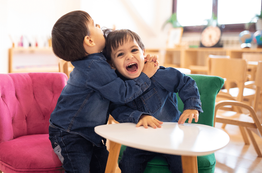 Toddler twins hug one another in a virginia child care center.